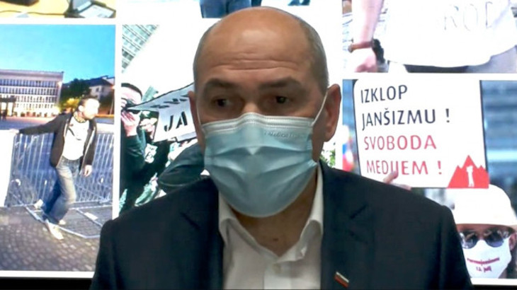 Screenshot of PM Janša during his videocall where he used changing backgrounds to show how he is allegedly the one under attack and not Slovenian journalists